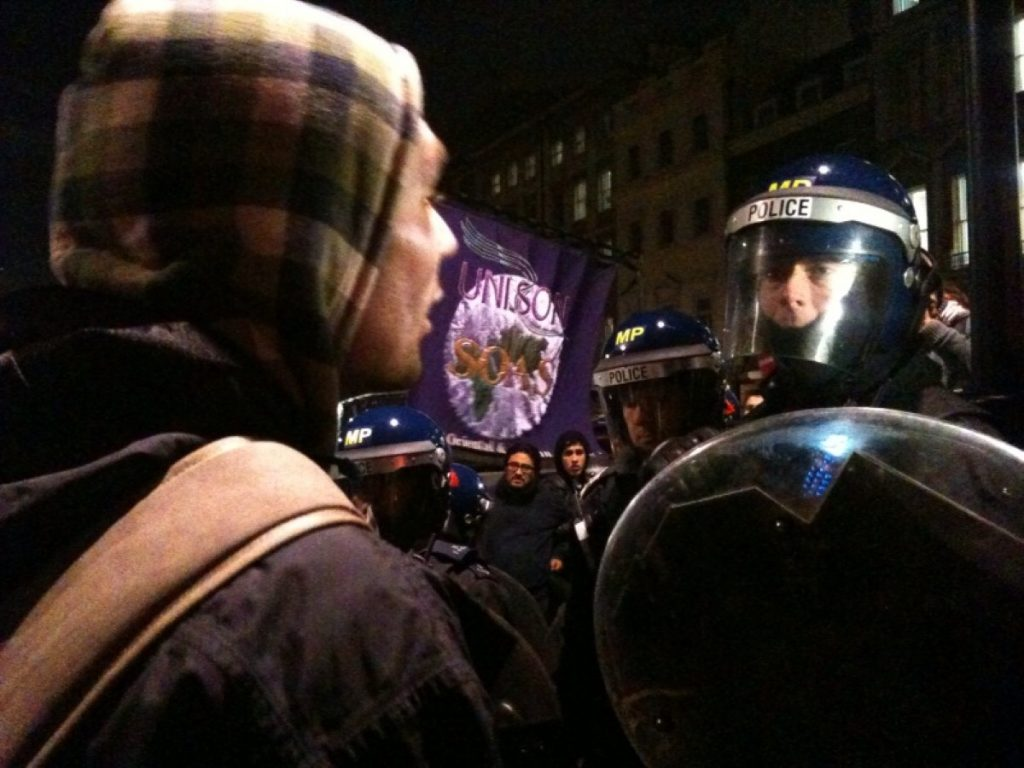 A protestor confronts a policeman in Whitehall during the tuition fees demonstration