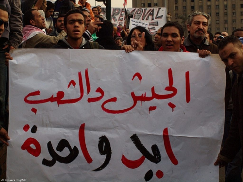 A banner reads 'the army and the people are one' during a protest before the Egyptian revolution in 2011.