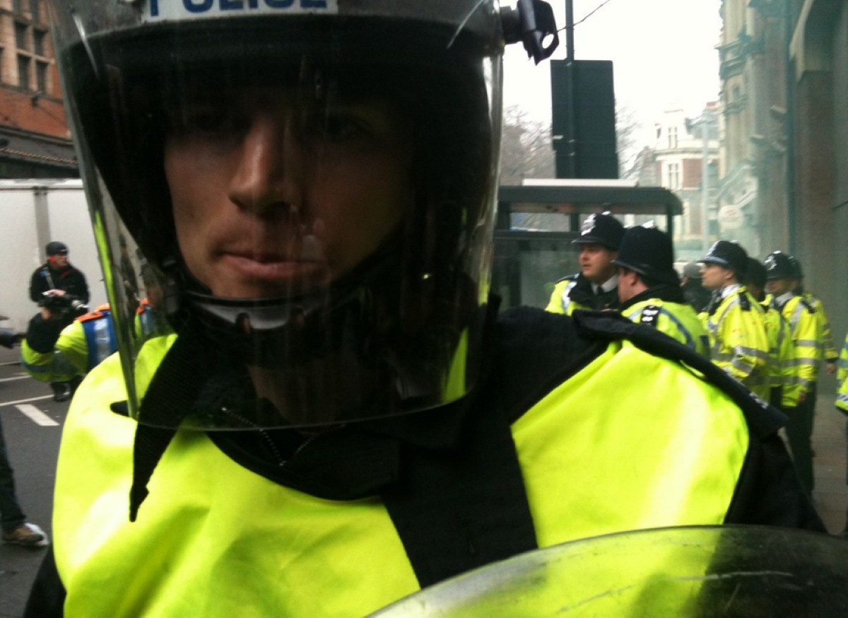 A riot policeman looks on as violent protests take place against spending cuts last month