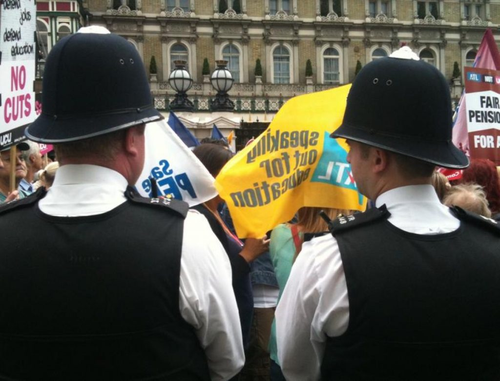 Two policemen watch the march during an earlier public sector strike.