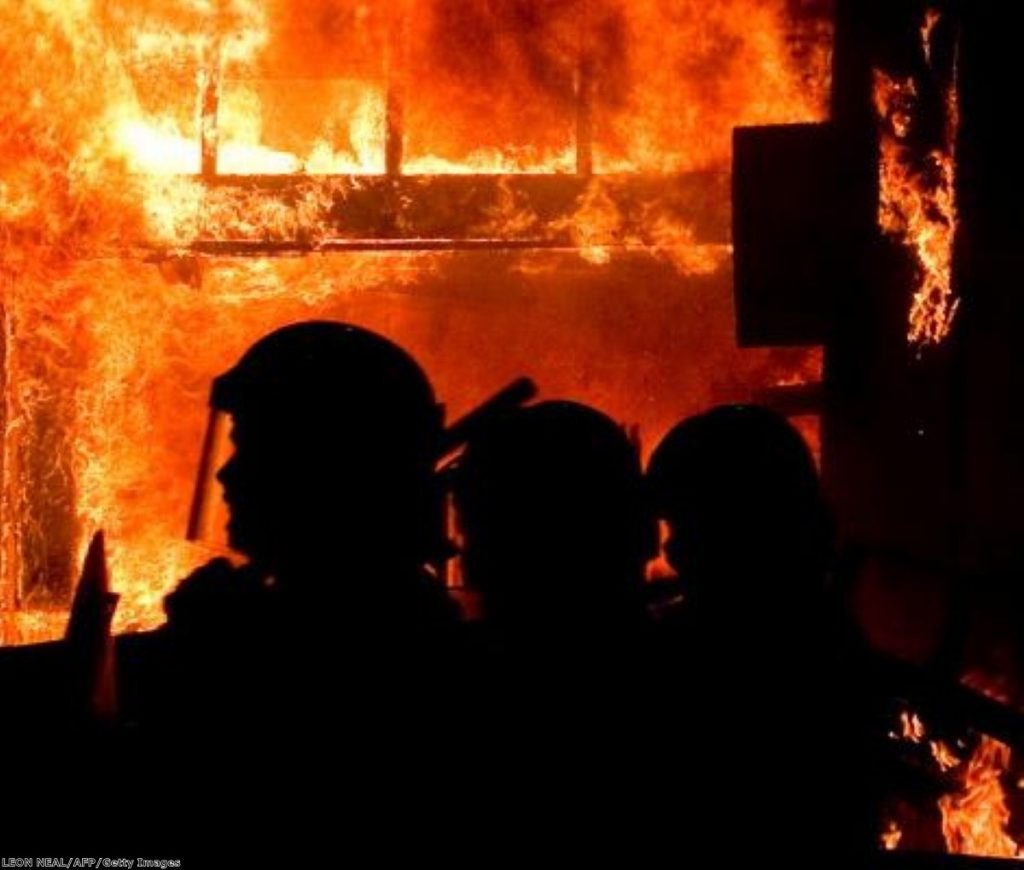 A shop burns in Tottenham, north London, as helpless riot police look on