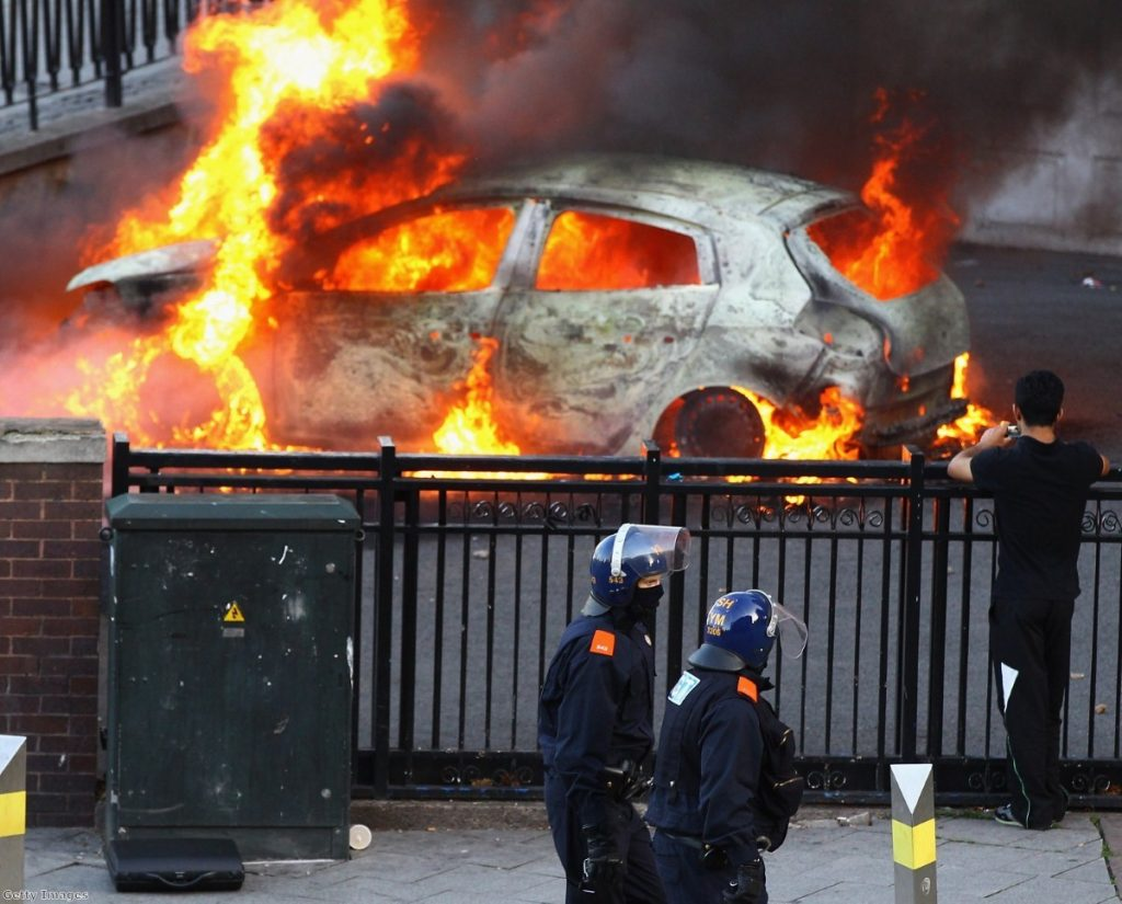 Police walk by a burning car during the height of the rioting. The disorder forced a re-think on gang policy.