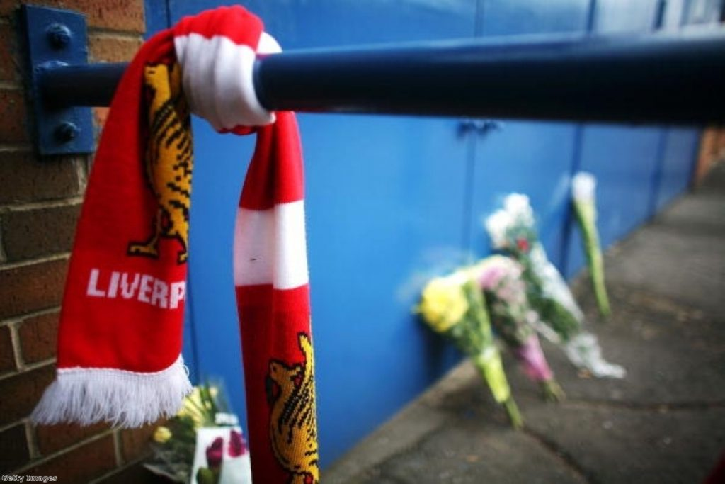 Floral tributes and Liverpool scarves lay in tribute next to the Leppings Lane entrance of Hillsborough Stadium