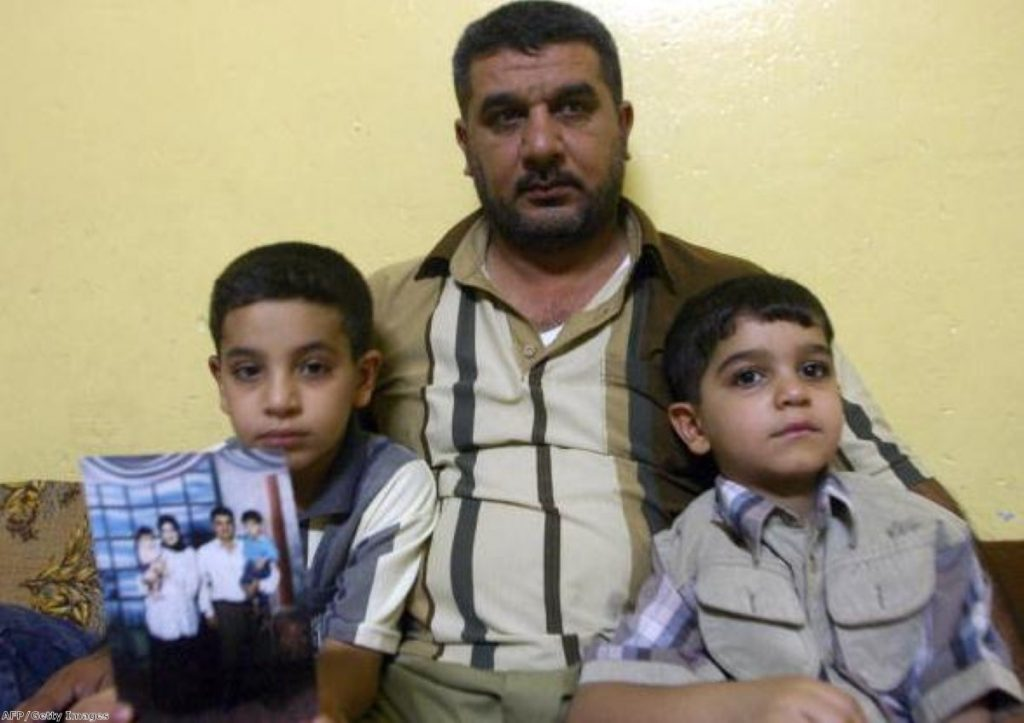 Baha Mousa's family: Hassan holds a family photo as he sits with uncle Alaa and younger brother Ali at their home in Basra