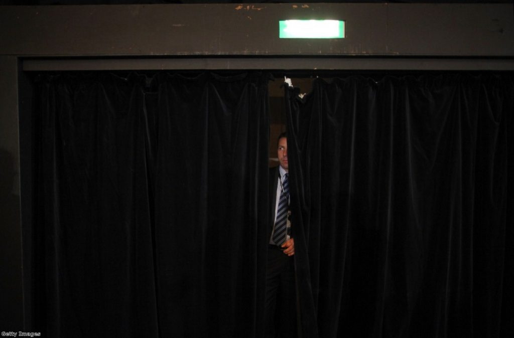 A member of security watches through a curtain while Nick Clegg conducts a Q&A in Birmingham. The party leadership was anxious about another vote on NHS reform.