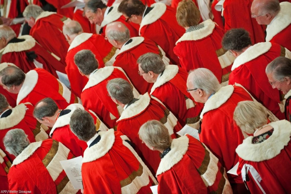 Members of the Lords, their existence threatened by this Queen's Speech, watch the monarch deliver her address to parliament