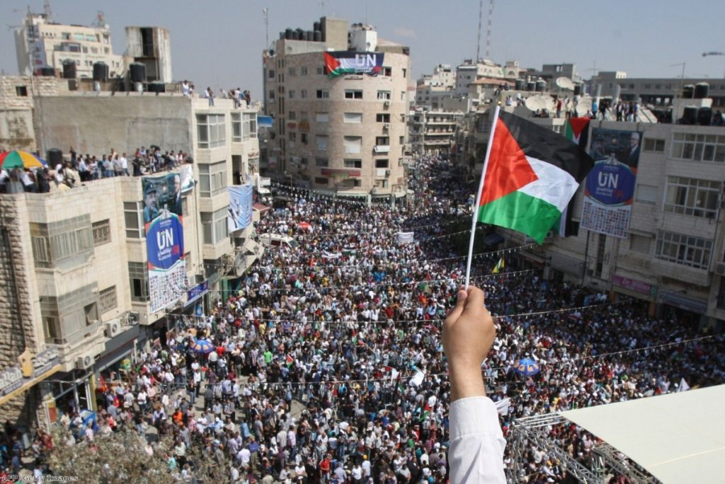 A Palestinian flag waves over the West Bank city of Ramalla yesterday as thousands gather to press for recognition at the UN.
