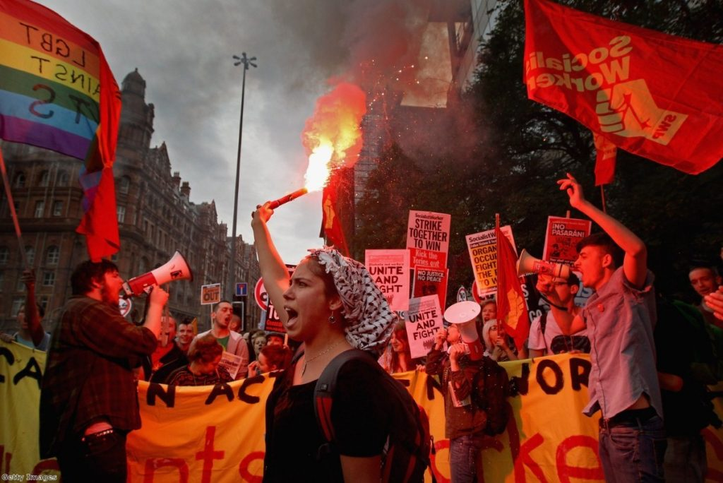 A demonstrator lights a flare during the march in Manchester.