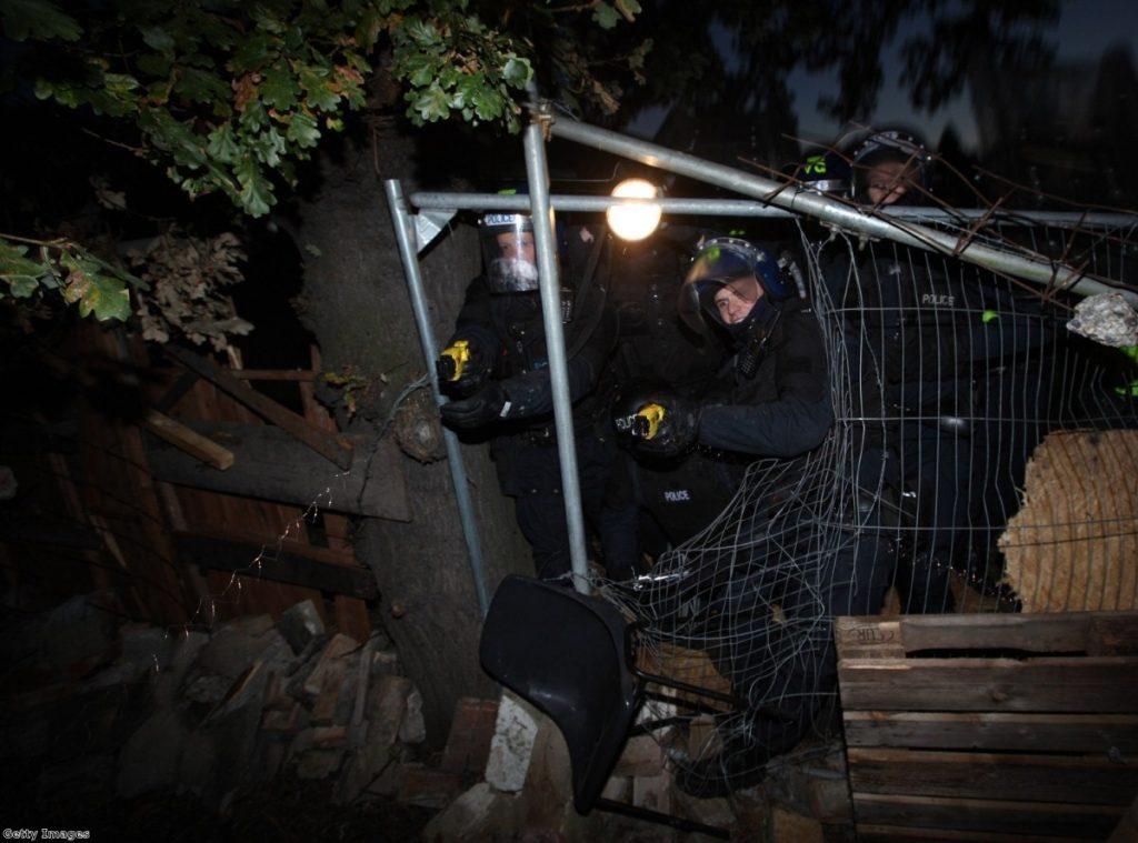 Police fire Tasers as they break through a barricade during evictions from Dale Farm travellers camp in 2011