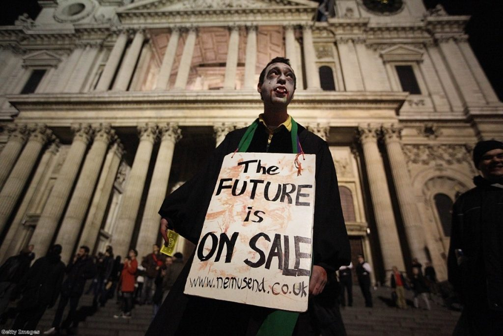A protestor dressed as a Zombie carries a placard in front of St Paul's