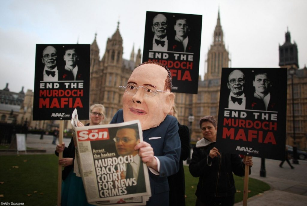 Campaigners await James Murdoch outside parliament today