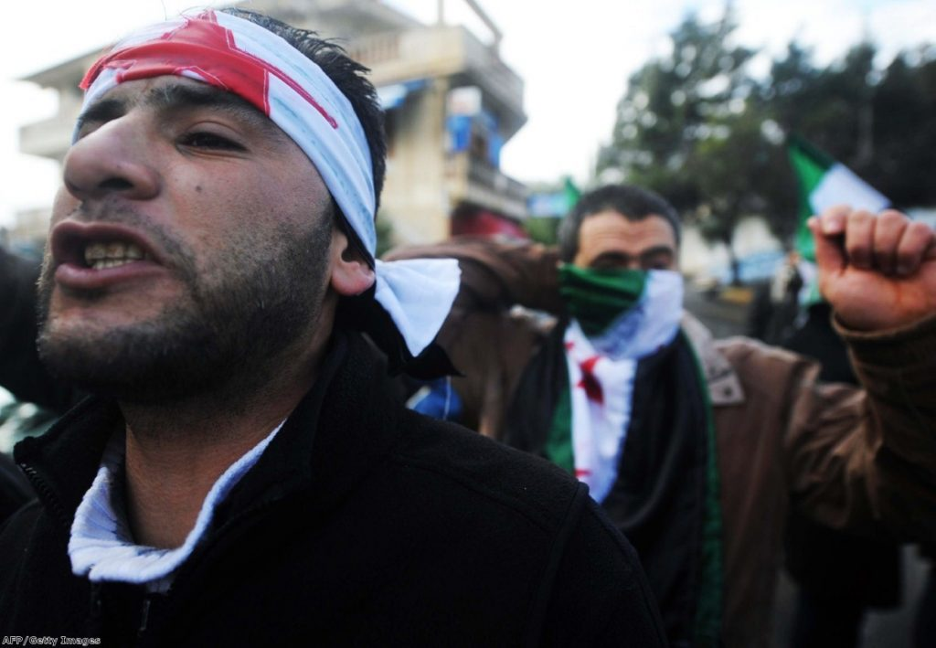 Men protest against Syrian repression in Algeria over the weekend. The violence has prompted outrage across the globe.
