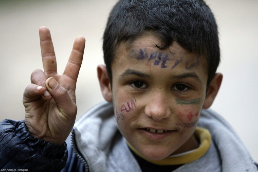 A young Syrian refugee fleeing violence in Homs flashes the 'V for Victory' sign