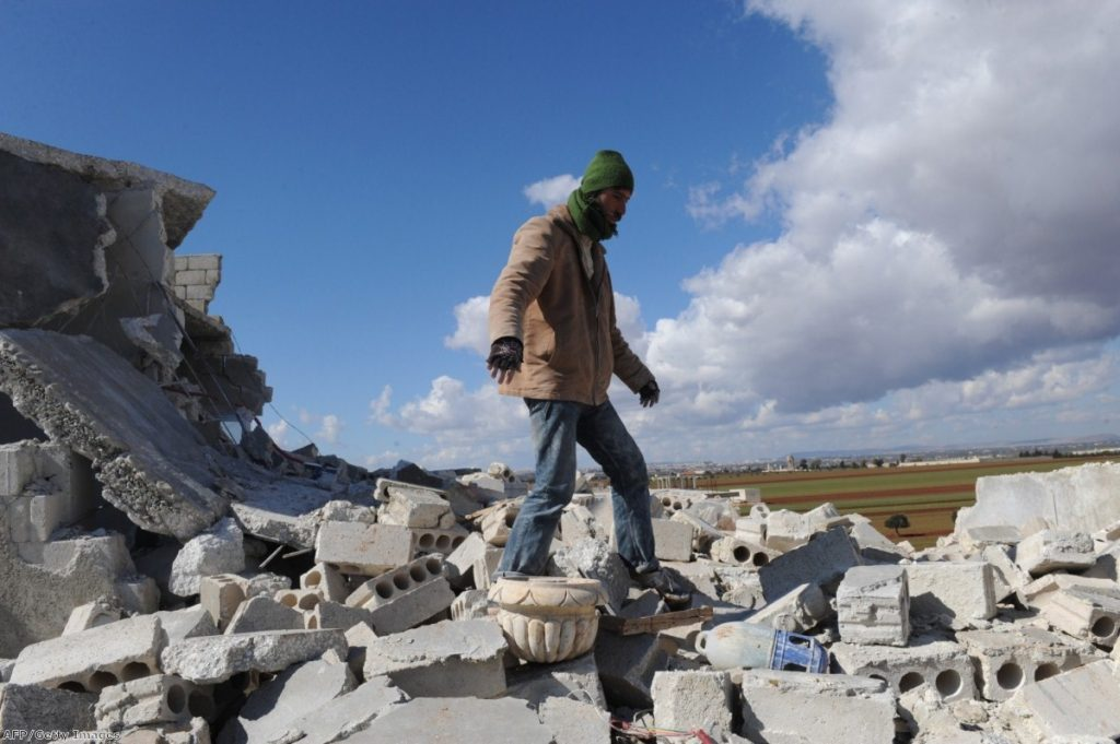 A man in the rubble of his home in Idlib, Syria