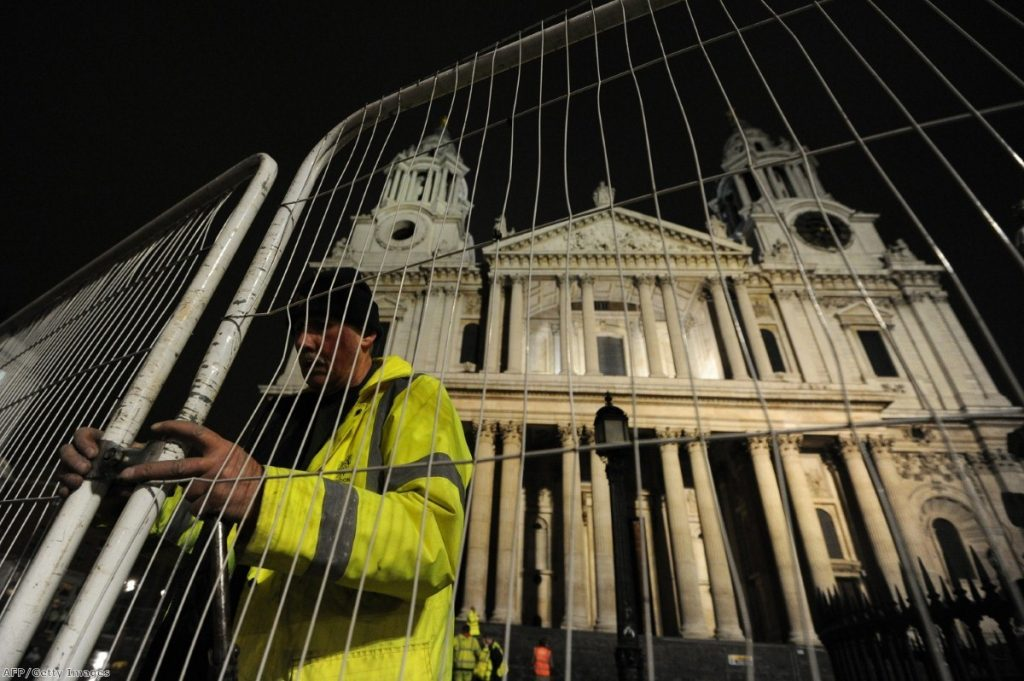 A worker erects a fence near Saint Paul's after police and bailiffs evicted protesters.