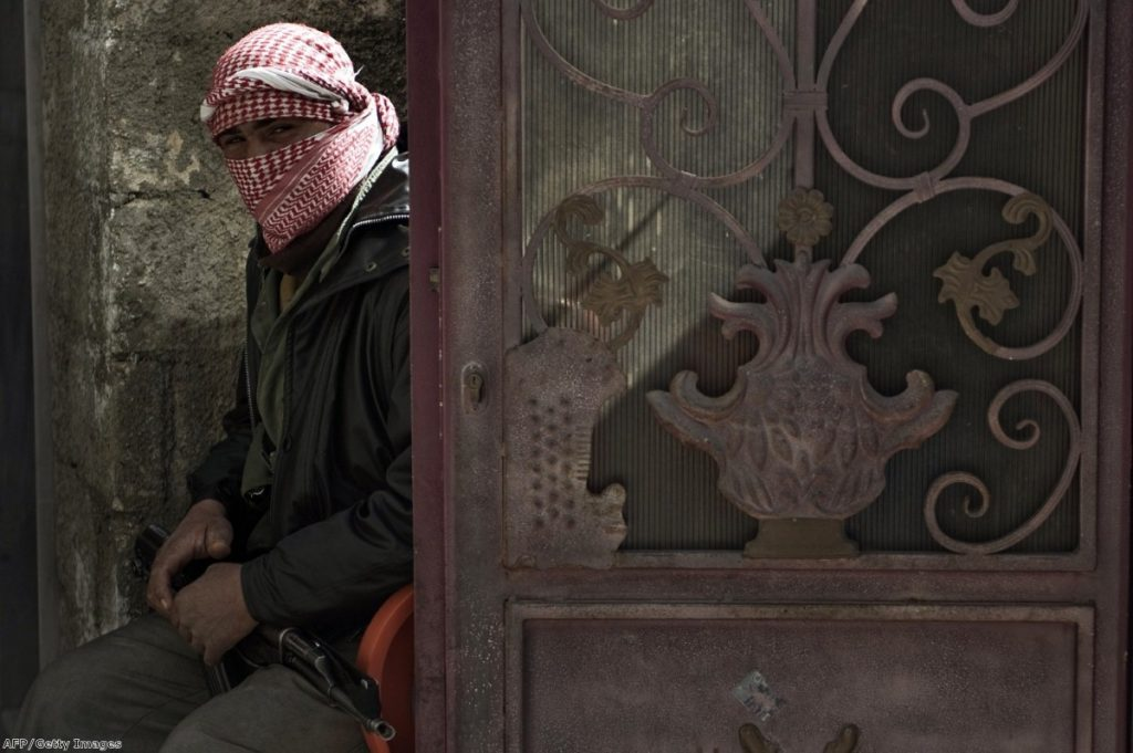 A Free Syria Army rebel waits as the conflict drags on