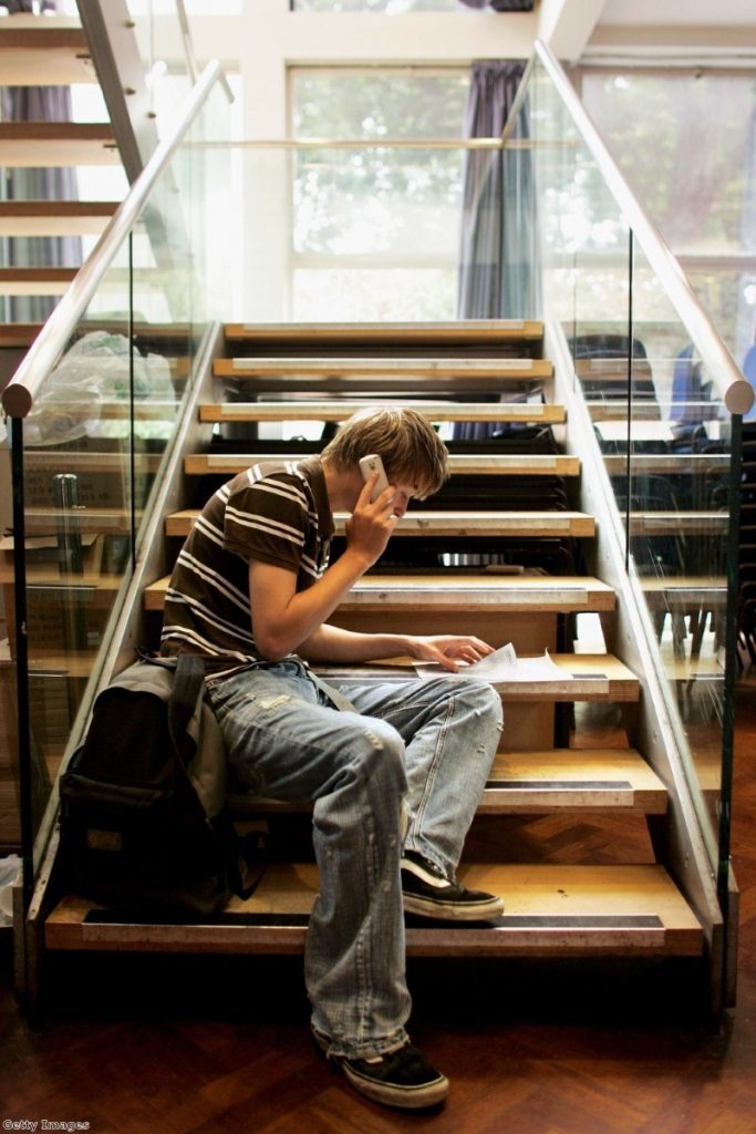 A GCSE students reads out his results on the phone. Many will be disappointed with their grades after a mew system was introduced.