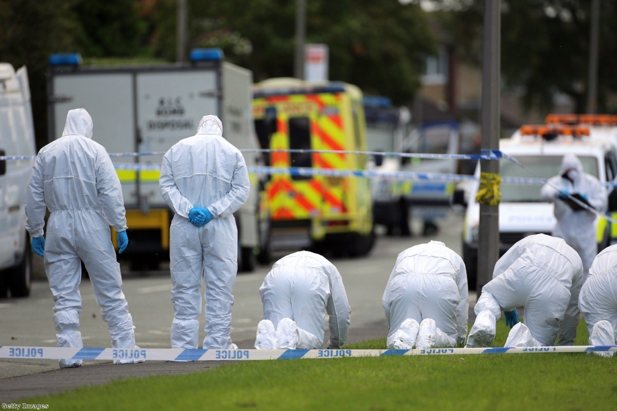 Forensic officers search the scene outside a house in Hattersley, Tameside where two female police officers were shot today