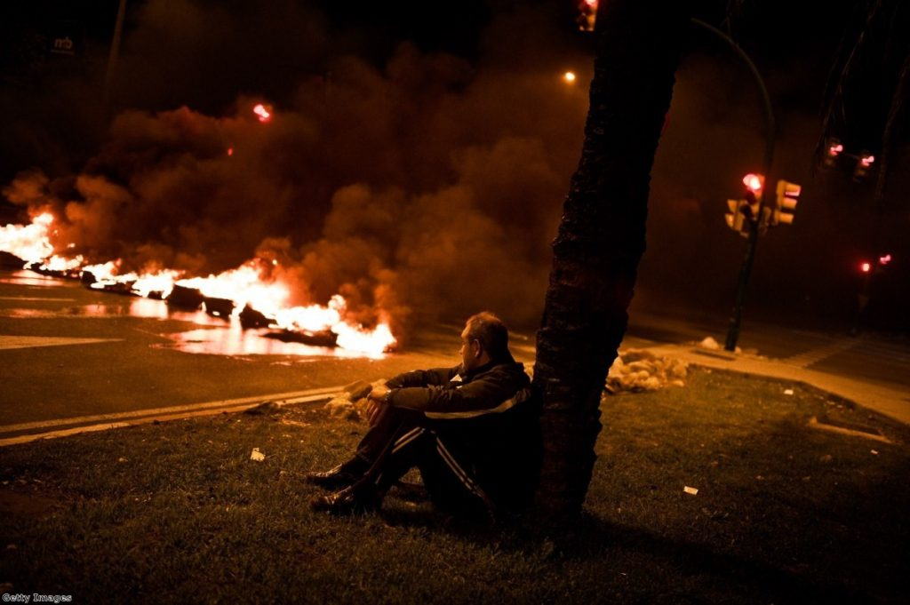 A demonstrator sits next to a barricade of burning tires at the main entrance of Mercabarna, the biggest wholesale market in Madrid, last night.