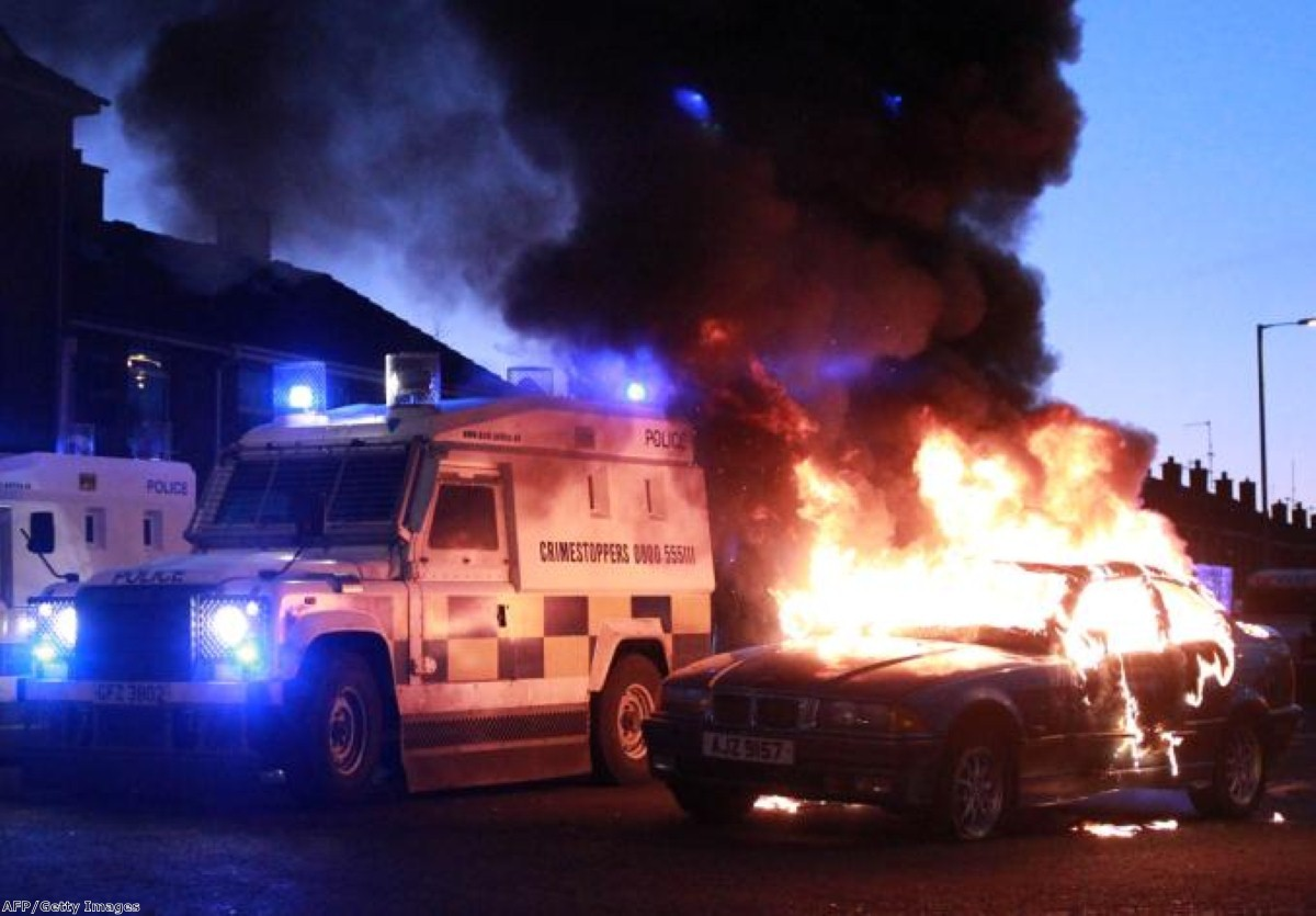 Police attend a burning vehicle in Belfast unrest caused by the flag decision