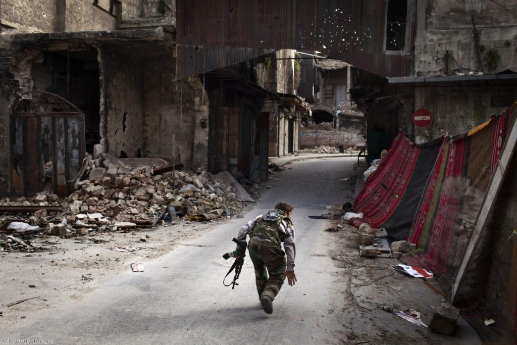 Syria: A rebel fighter tries to avoid sniper fire in Aleppo earlier this year. The debate on whether to supply rebel forces with weapons is unlikely to die down.