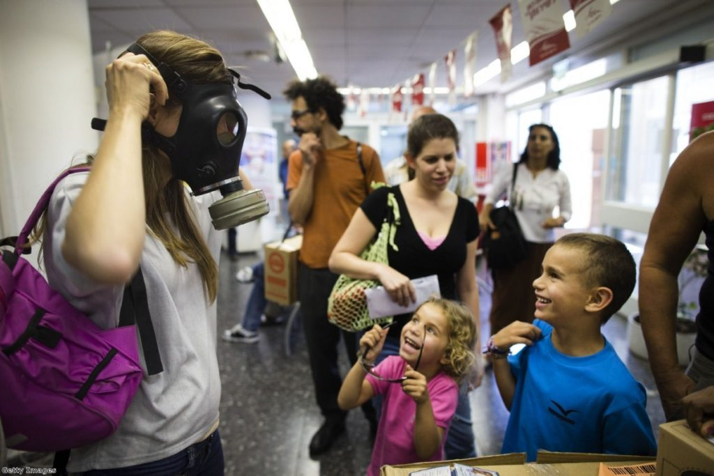 An Israeli woman shows her children how to put on a gas mask yesterday  in Tel Aviv, amid tensions over possible military action in Syria