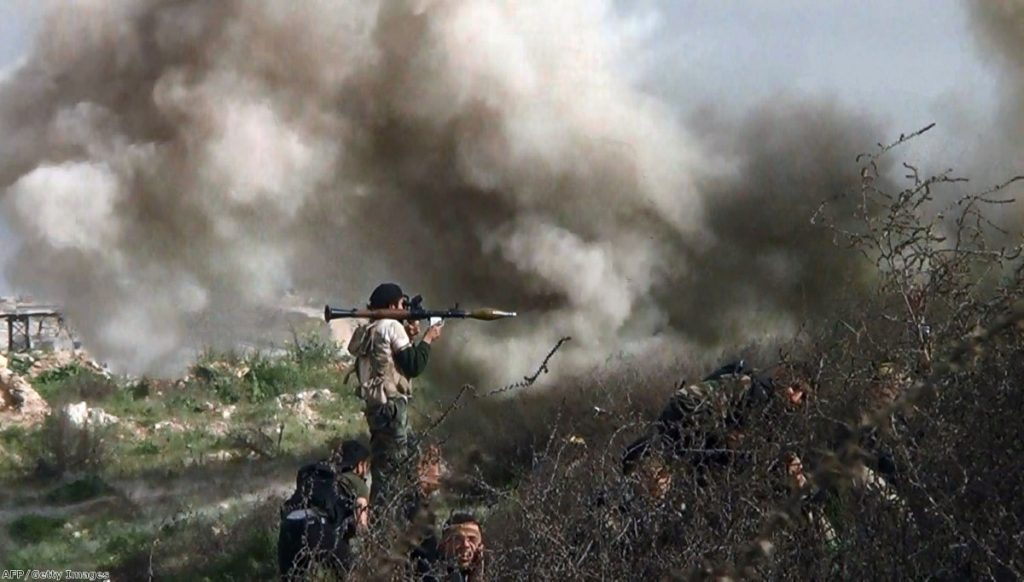 An opposition fighter holding a rocket propelled grenade (RPG) as his fellow comrades take cover from an attack by regime forces in Khanasser on Monday