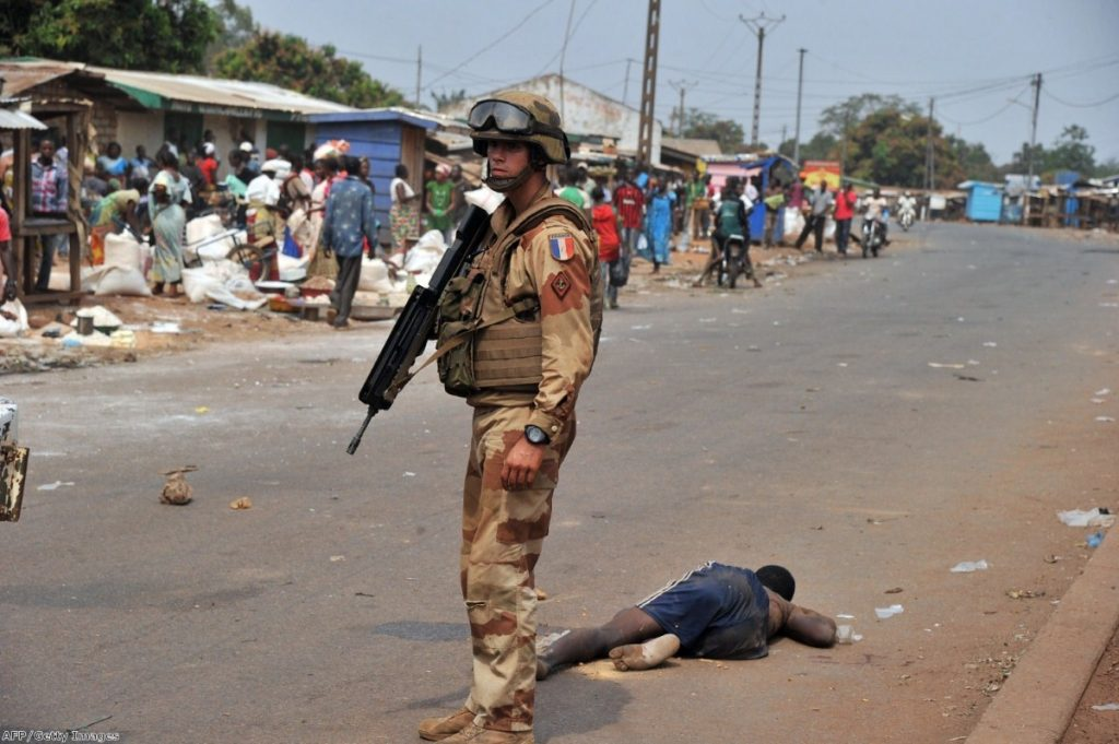 A French soldier stands by the body of a Muslim man who was reportedly beaten to death by a crowd in the north of Bangui last Friday.