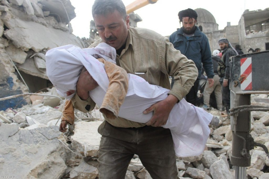 A Syrian man carries a body out of the rubble following air raids by government forces