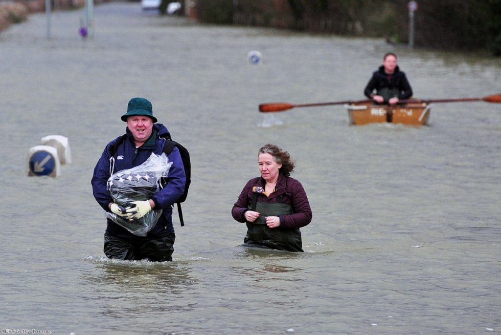 A couple wade along a flooded road near Egham, west of London, yesterday.