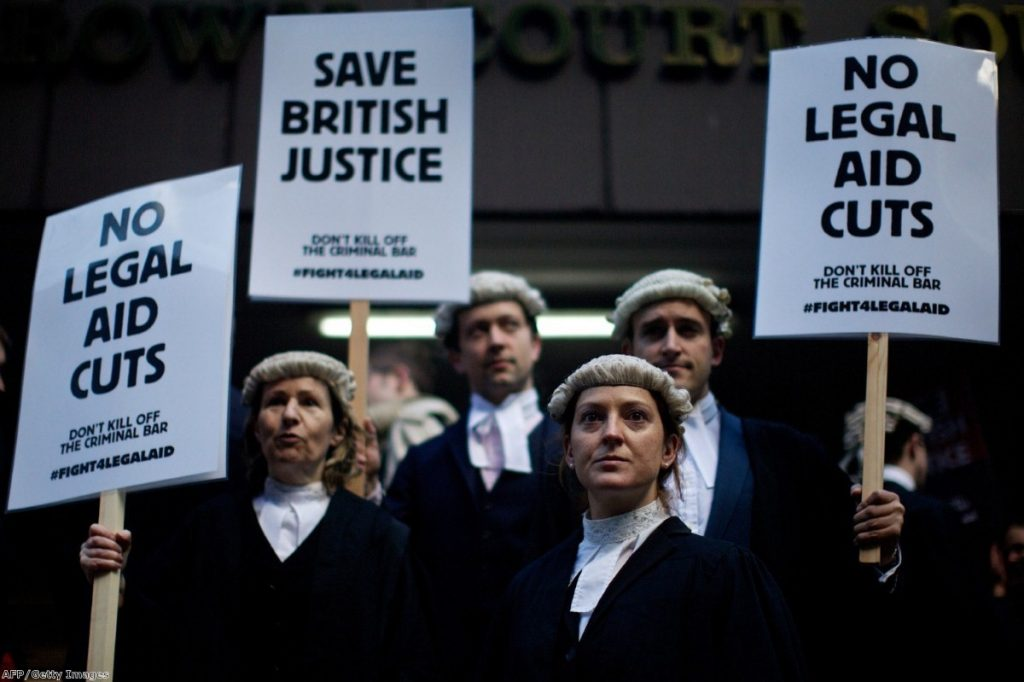 Legal professionals hold placards during a protest against cuts to legal aid outside Southwark Crown Court in January