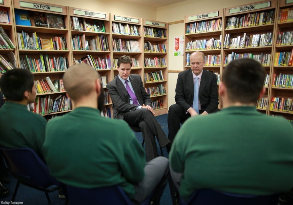 Clegg and Grayling speak to inmates in a prison library - the Lib Dems have stood shoulder-to-shoulder with the justice secretary over the prisoner book ban