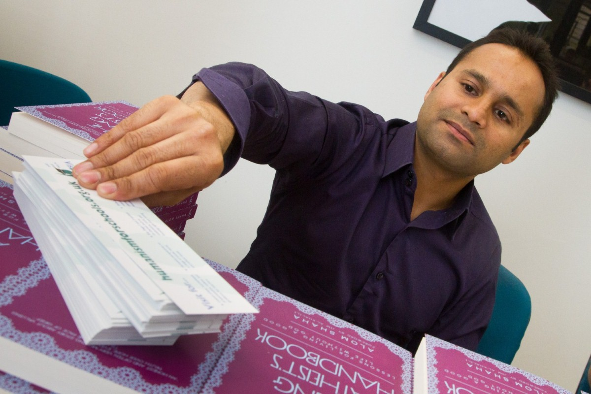 Alom Shaha with copies of his book before the launch