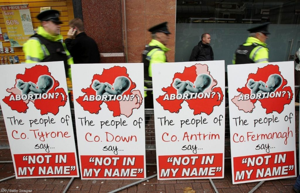 Police walk around anti-abortion placards outside the Marie Stopes clinic, the first private clinic to offer abortions to women in Belfast.