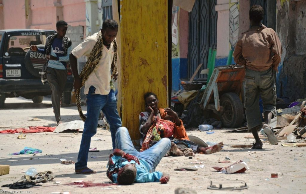 A Somali man looks down at a blast victim as a wounded Somali mother holds her two children, one wounded and one dead, following a bomb attack in Mogadishu last month
