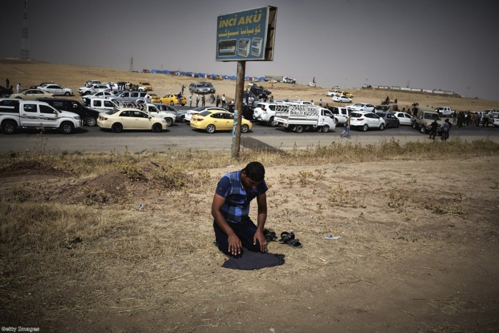 An Iraqi refugee fleeing from the city of Mosul prays at a checkpoint after Isis took the city last year