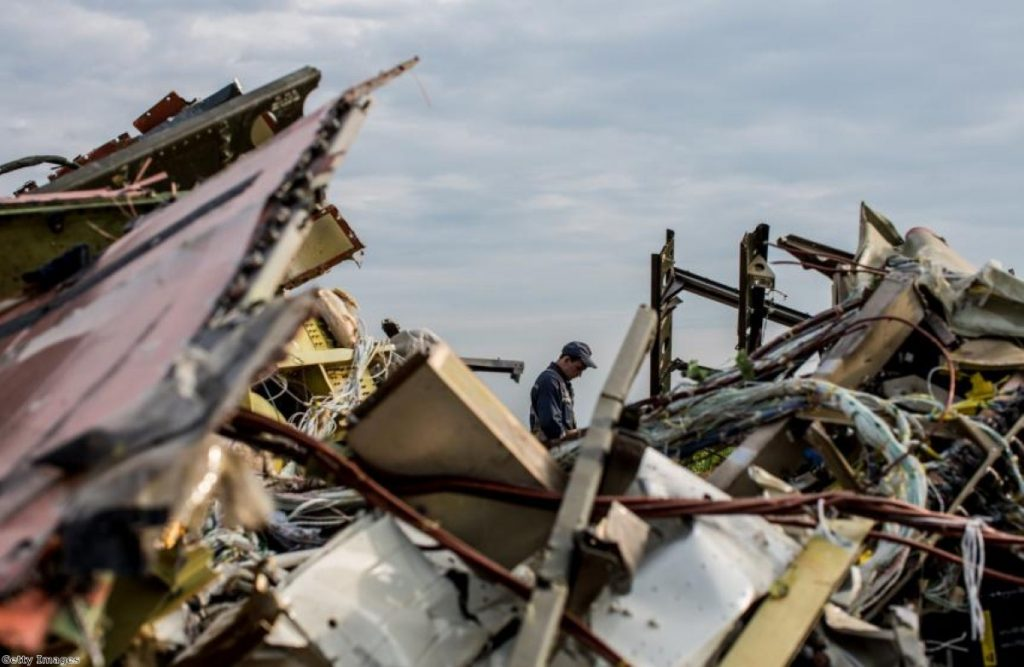 A man inspects the debris at the site of the downed MH17 aircraft