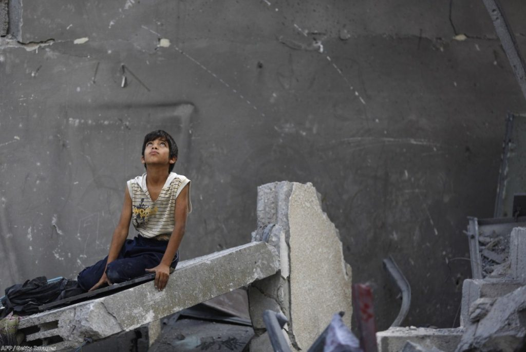 A Palestinian boy sits on the rubble of a destroyed building following an Israeli air strike in the center of Gaza City on July 22, 2014