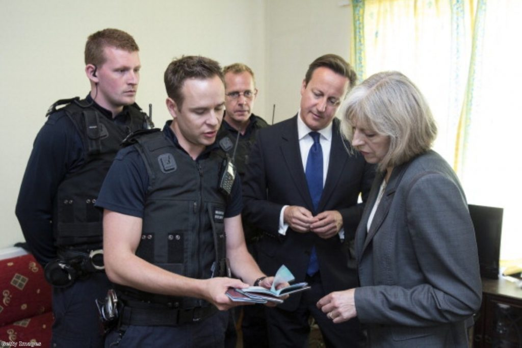 David Cameron and Theresa May with immigration enforcement officers