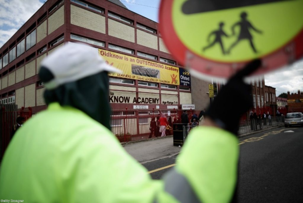 A lollipop person looks on at one of the Birmingham schools implicated in the Trojan Horse plot