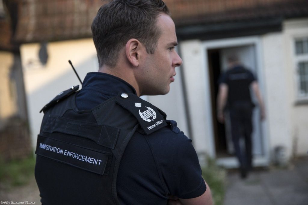 An immigration officer takes part in a raid on suspected undocumented migrants. Lawyers say up to 20 officers attend dawn raids against their clients.