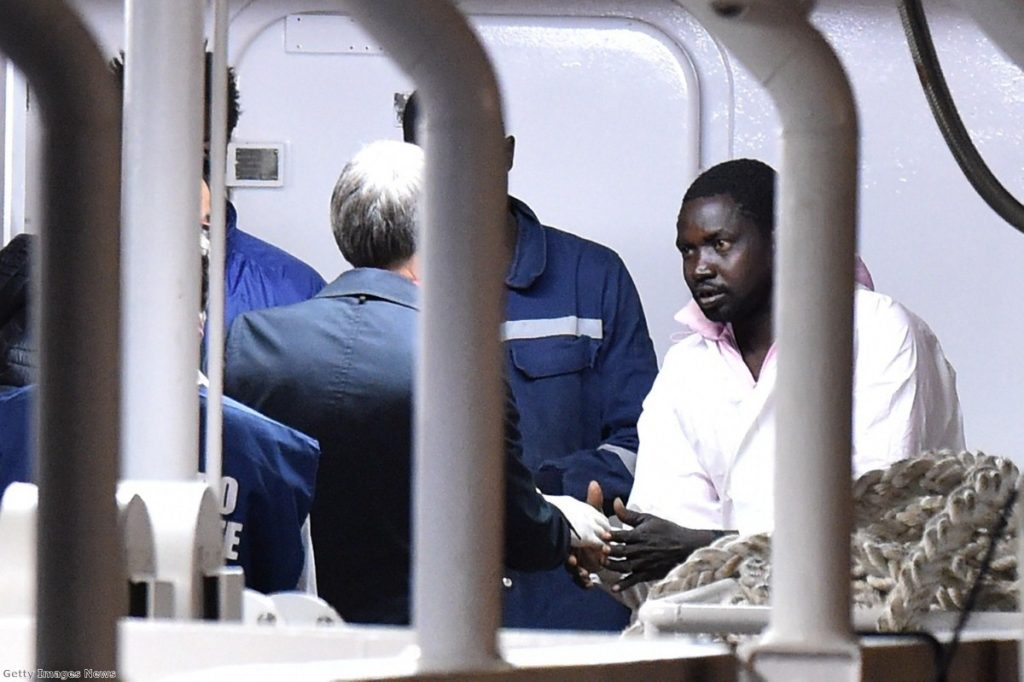 Italian minister Graziano Delrio shakes hands with a migrant standing on the deck of a boat carrying 27 survivors of the migrant shipwreck