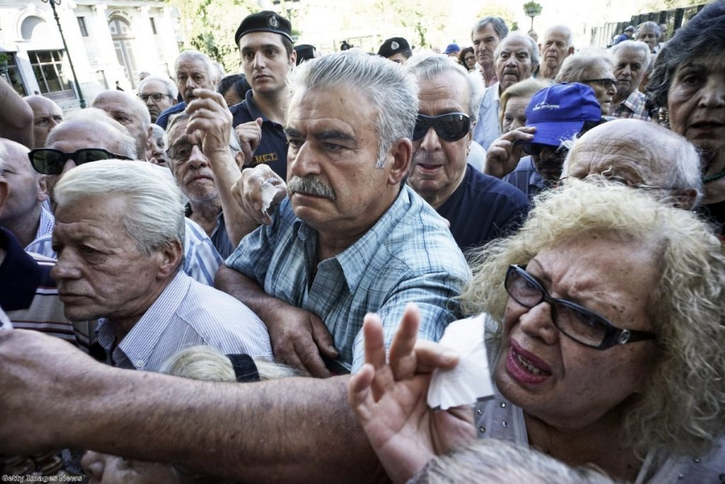 Pensioners line up outside a National Bank branch in Athens yesterday after they open to allow them a small part of their benefits