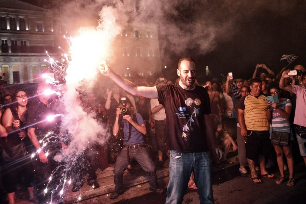 Greeks celebrate in front of the their parliament as the results from last night's vote start to come in