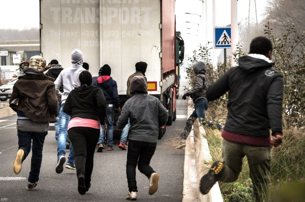 Migrants and asylum seekers try to get into the UK on the back of lorries in Calais