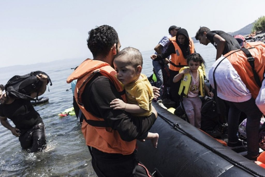 Family arrives on Greek beach, after crossing, on an inflatable boat with 35 people