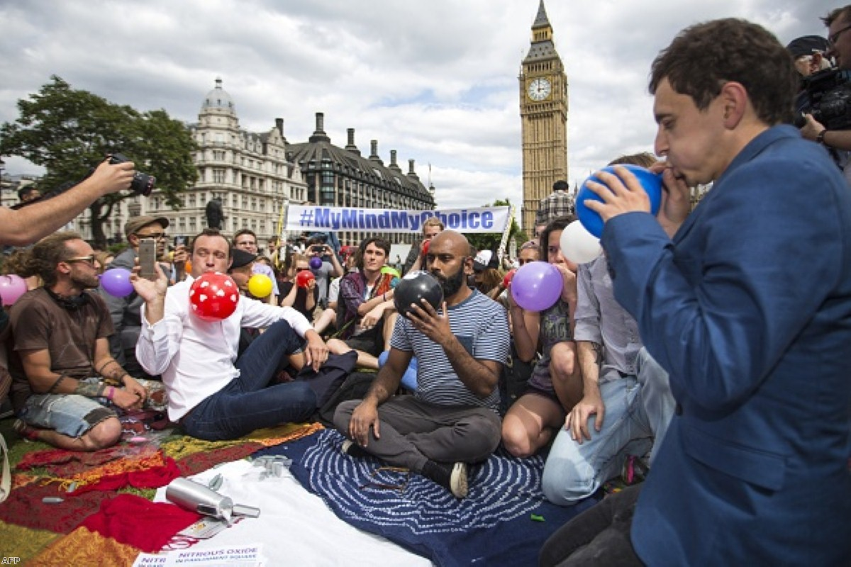 Protesters stage a mass inhalation of laughing gas, outside the Houses of Parliament