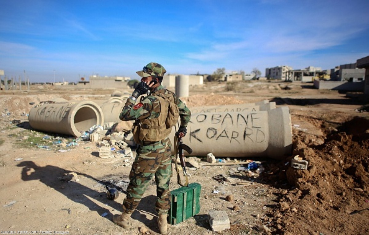 A Kurdish Peshmerga fighter talks on the phone during fighting against Islamic State