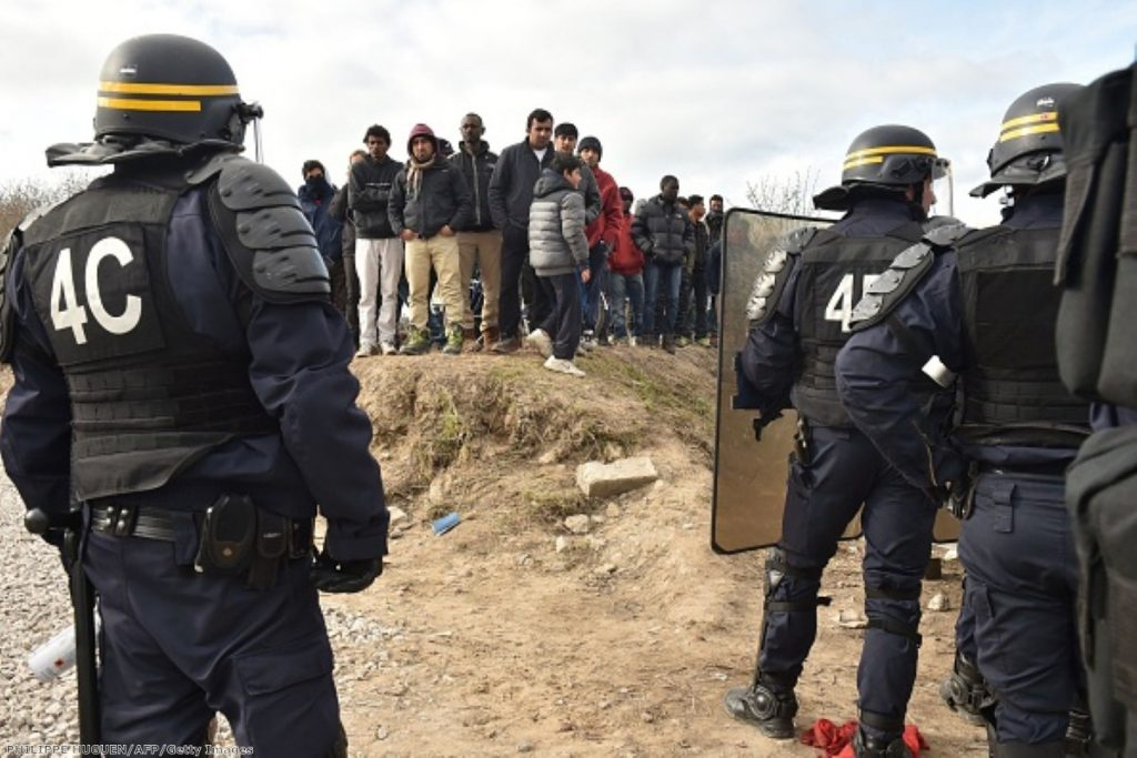 Anti-riot police face migrants during the dismantling of half of the 'Jungle' migrant camp in Calais