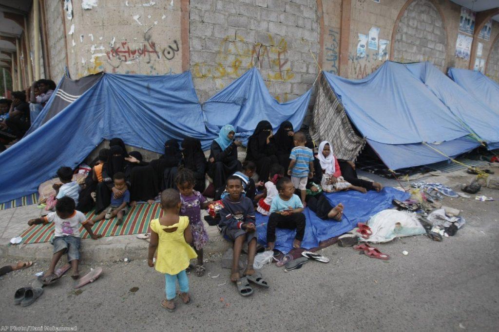Eritrean female asylum seekers sit along with their children on the sidewalk in Yemen